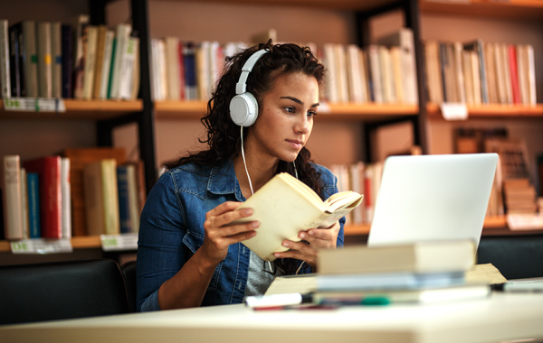 Young lady reading a book with headphones one